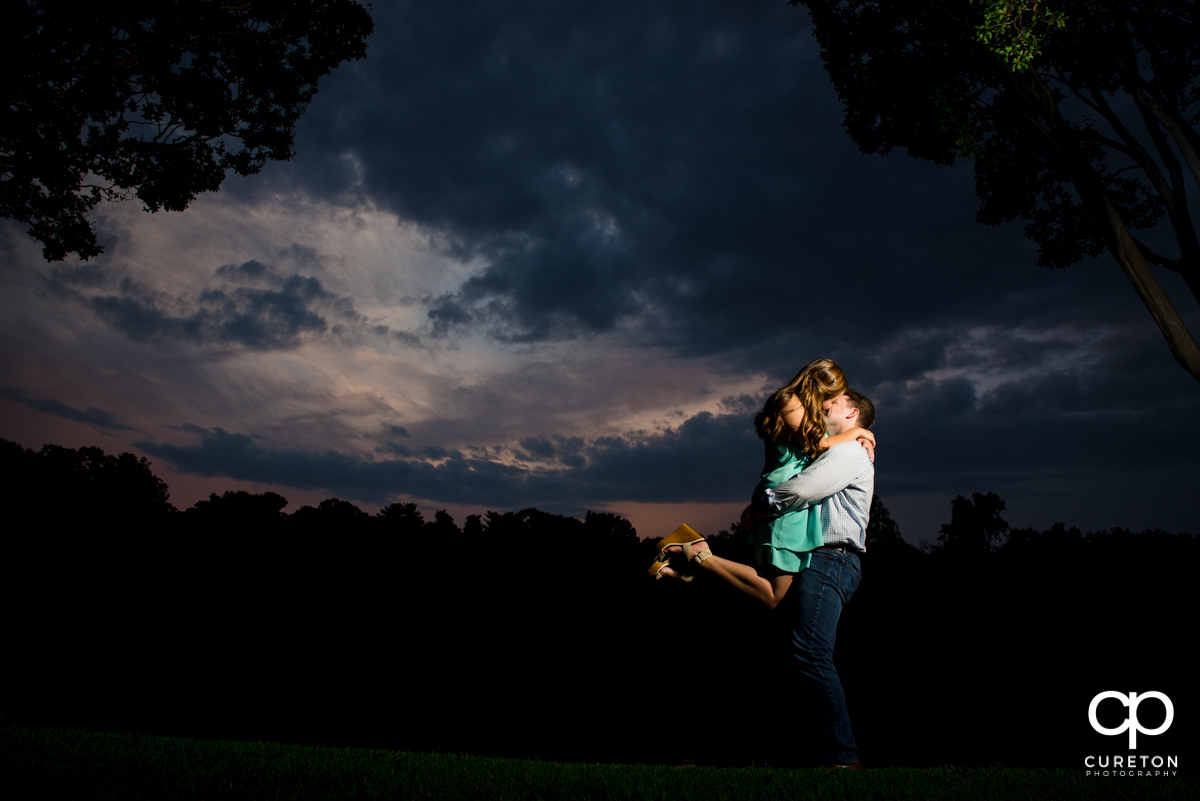 Man lifting his future bride by the lake during their sunset engagement session in Greenville,SC.