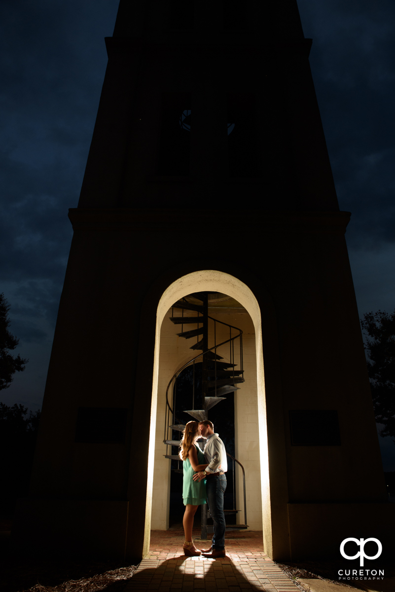 Engaged couple kissing in the Bell Tower at Furman.