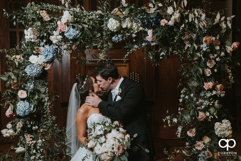 Bride and groom kissing in the middle of a gorgeous flower arch at Daniel Chapel at Furman university.