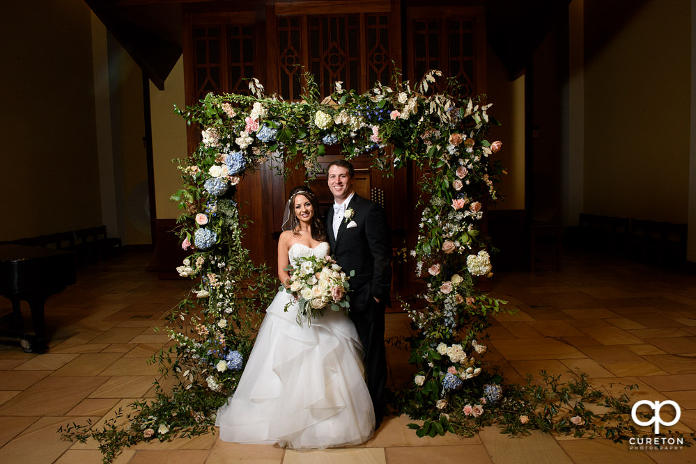 Newlyweds standing in the middle of a gorgeous flower arch.