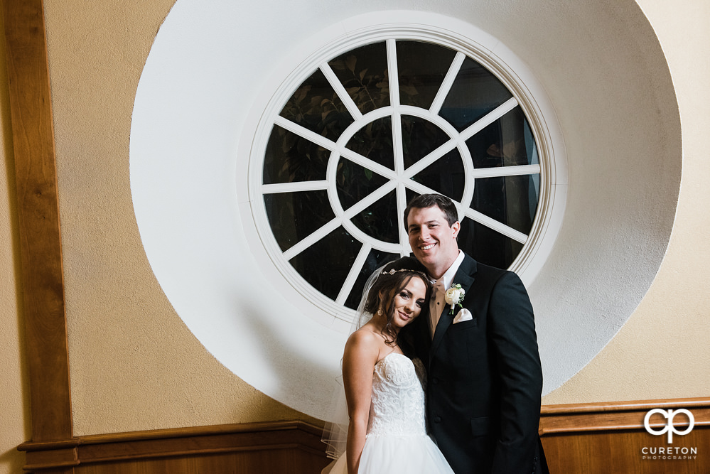 Bride and groom standing in a circular window.