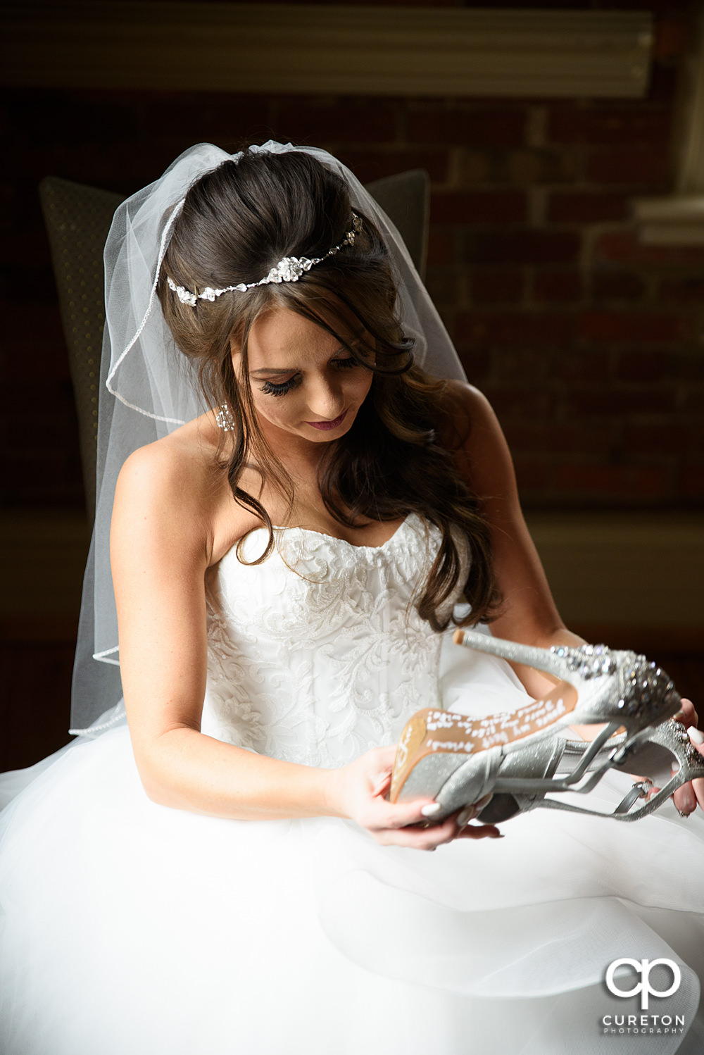 Bride reading a note left on her shoes.