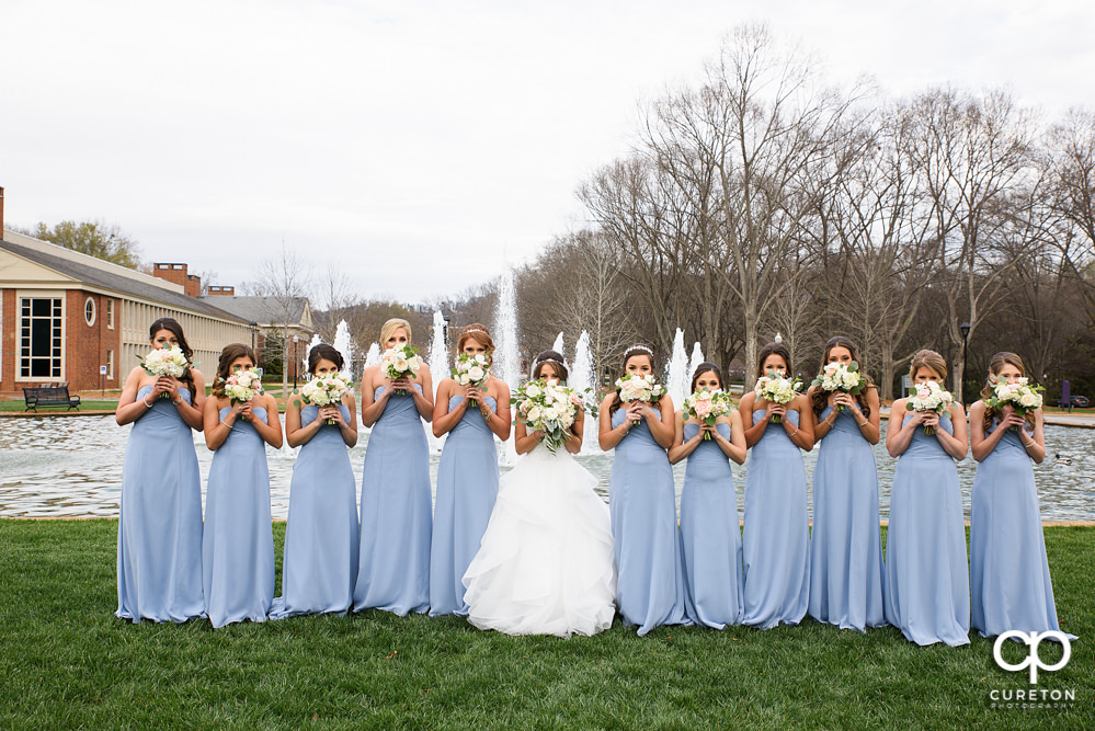 Bridesmaids with flowers over their faces.