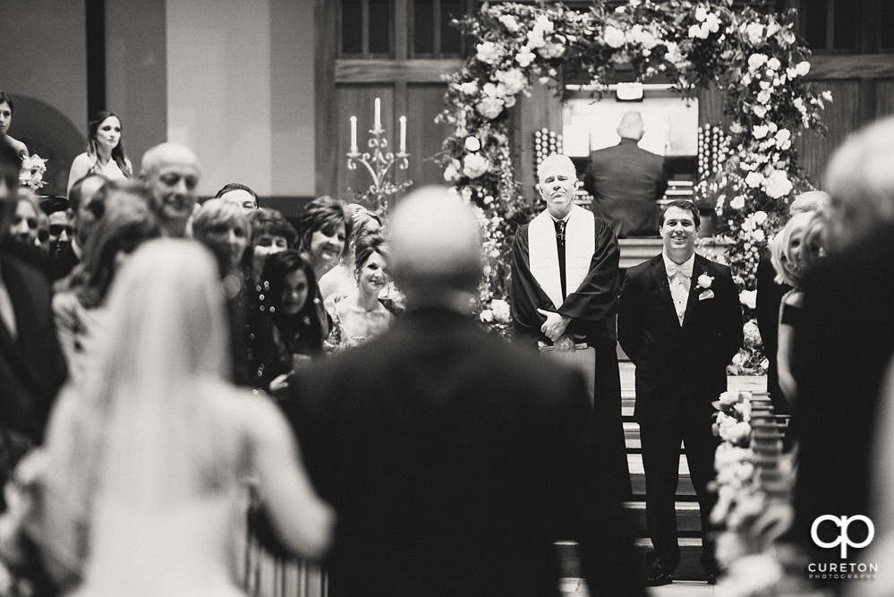 Groom smiling as he sees his bride for the first time walking down the aisle at Daniel Chapel.