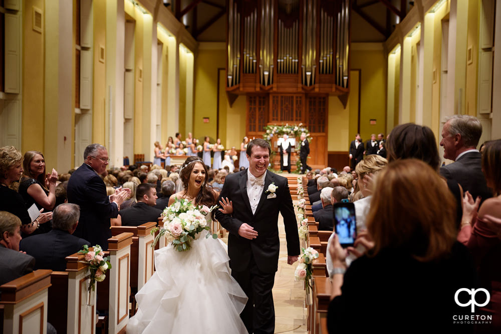 Bride and groom walkign down the aisle after their wedding at Daniel Chapel.
