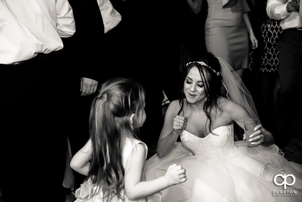 Bride and the flower girl dancing.