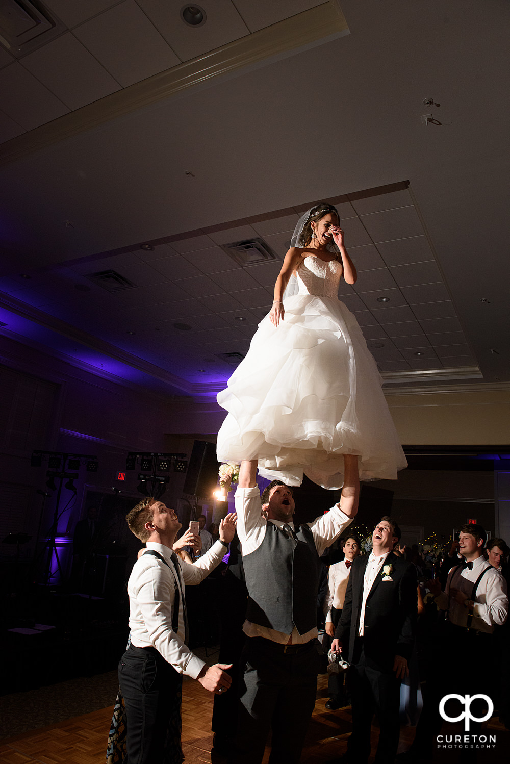 Bride performing a cheer stunt at her wedding.