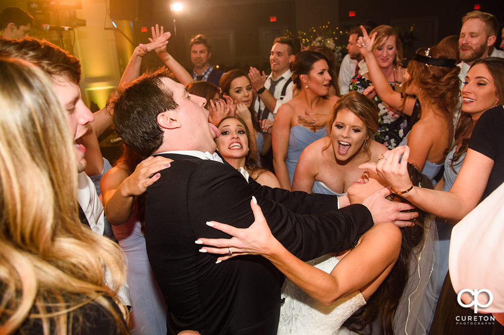 Groom kissing his bride on the dance floor.
