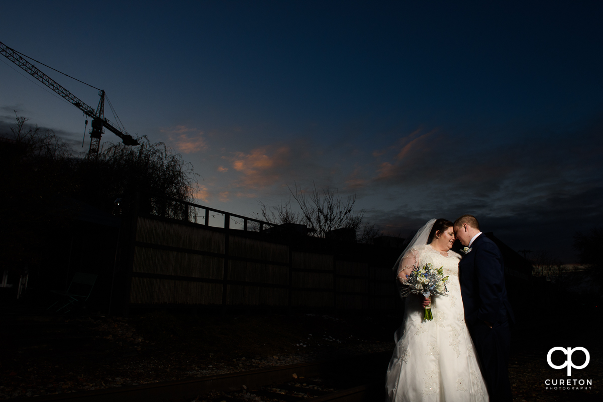 Bride and Groom cuddling after their December Old Cigar Warehouse wedding in Greenville,SC.