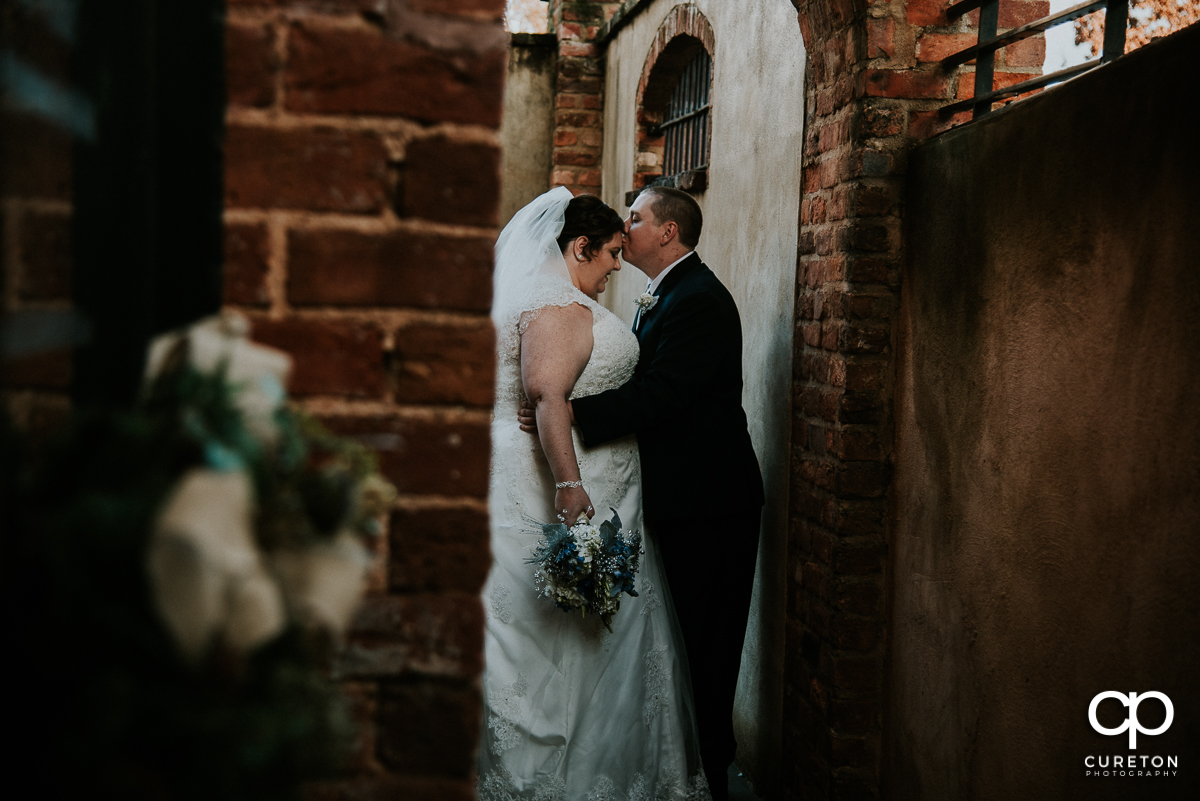 Groom kissing his bride on the forehead before their December Old Cigar Warehouse wedding in Greenville,SC.