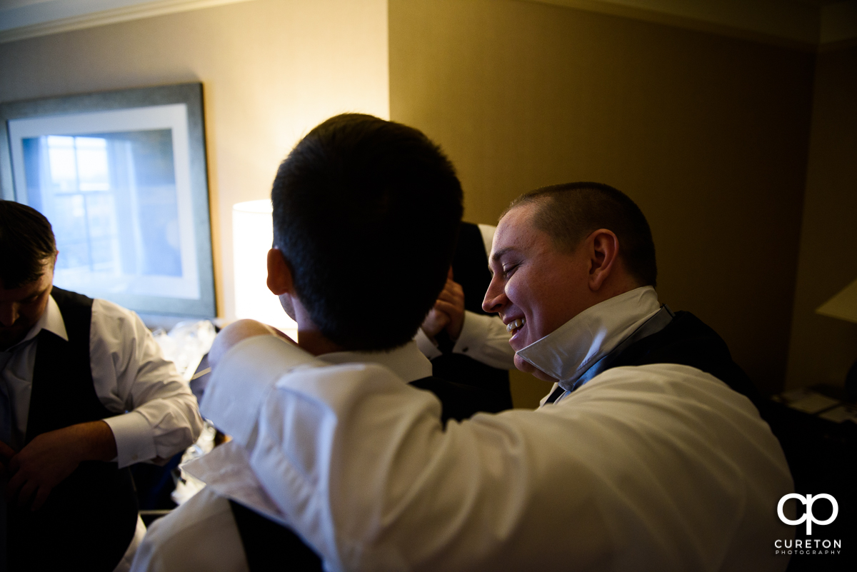Groom helping his friend with a tie.