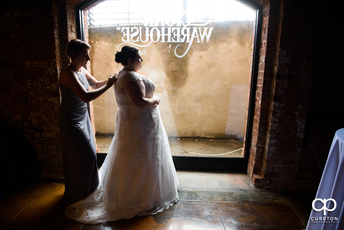 Bride getting her dress on at Old Cigar Warehouse.