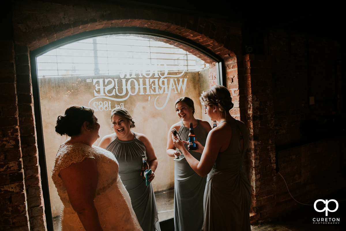 Bride and bridesmaids having a drink before the wedding at the Old Cigar Warehouse.