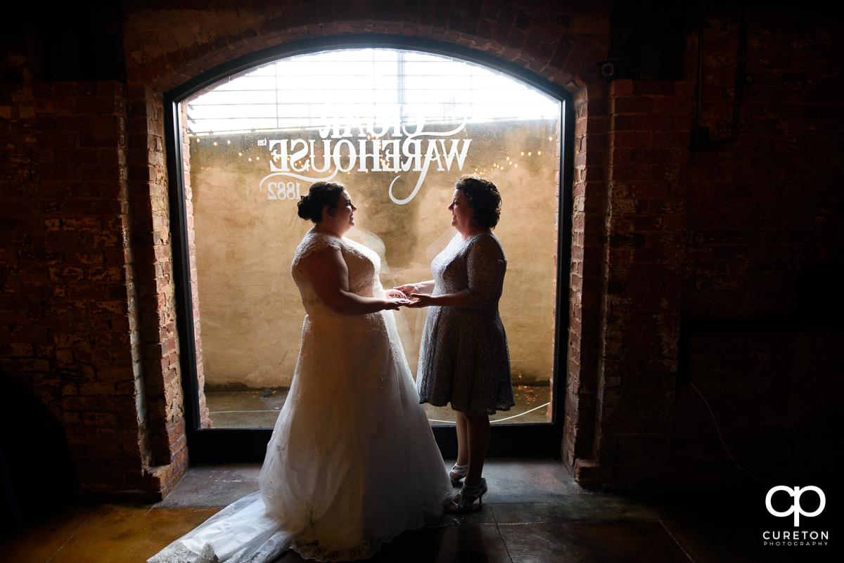 Bride and her mother standing in the window of The Old Cigar Warehouse before the wedding.