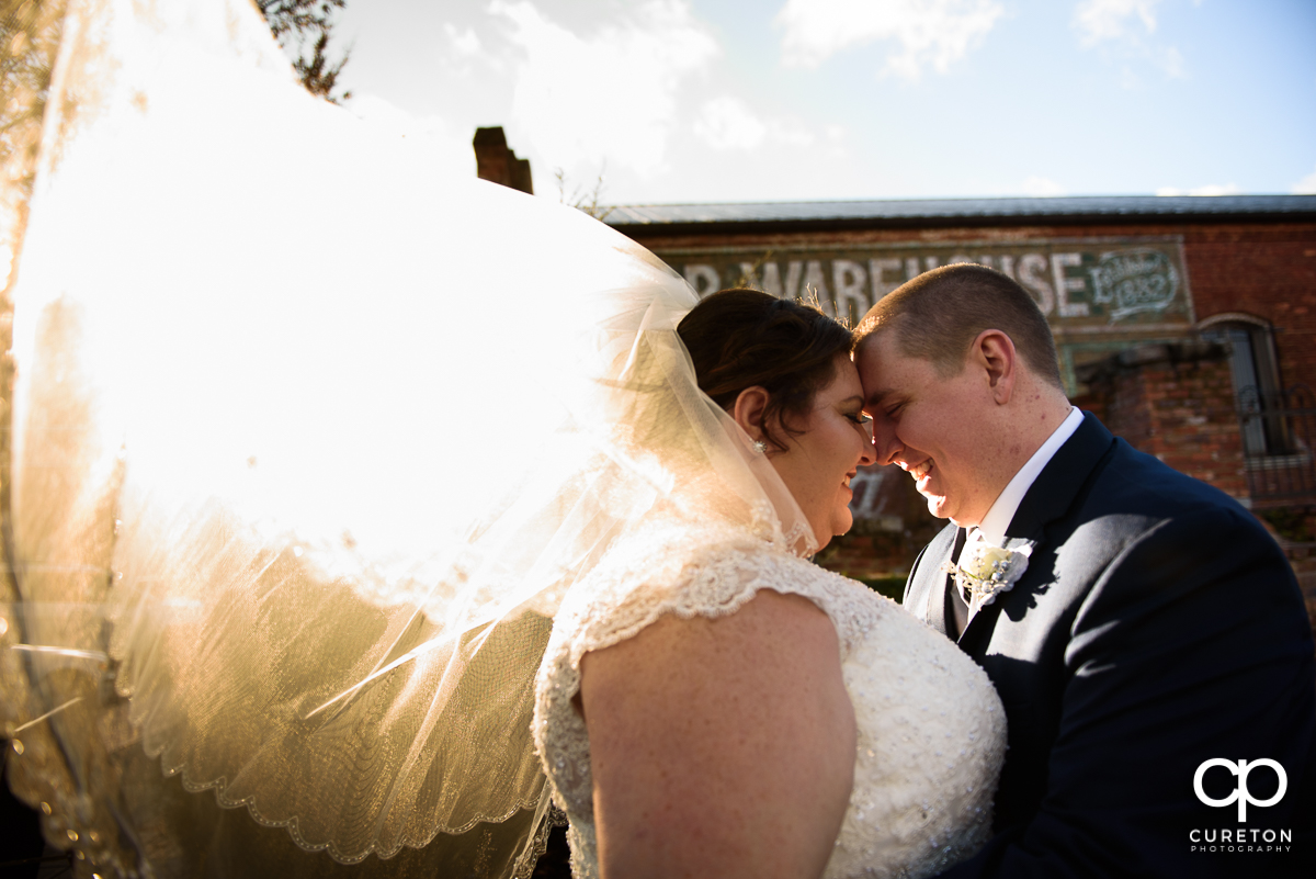 Bride hugging with her husband as her veil blows inth ewind and glowing sunlight at their December Old Cigar Warehouse wedding.
