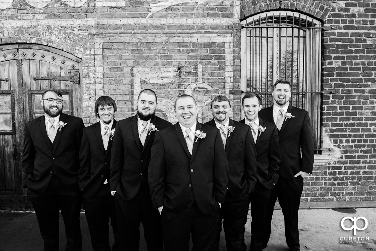 Groom and groomsmen laughing on the deck of The Old Cigar Warehouse.