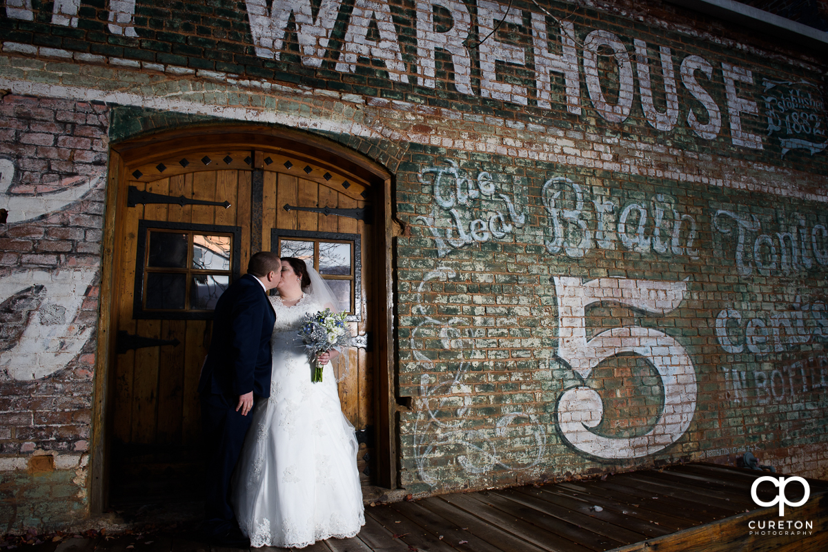Bride and groom kissing on the back deck of The Old Cigar Warehouse.