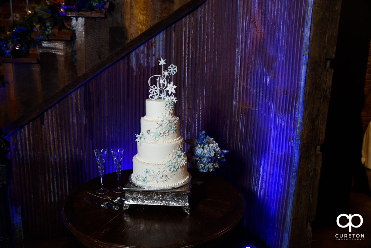 Winter themed wedding cake on a blue uplit backdrop.