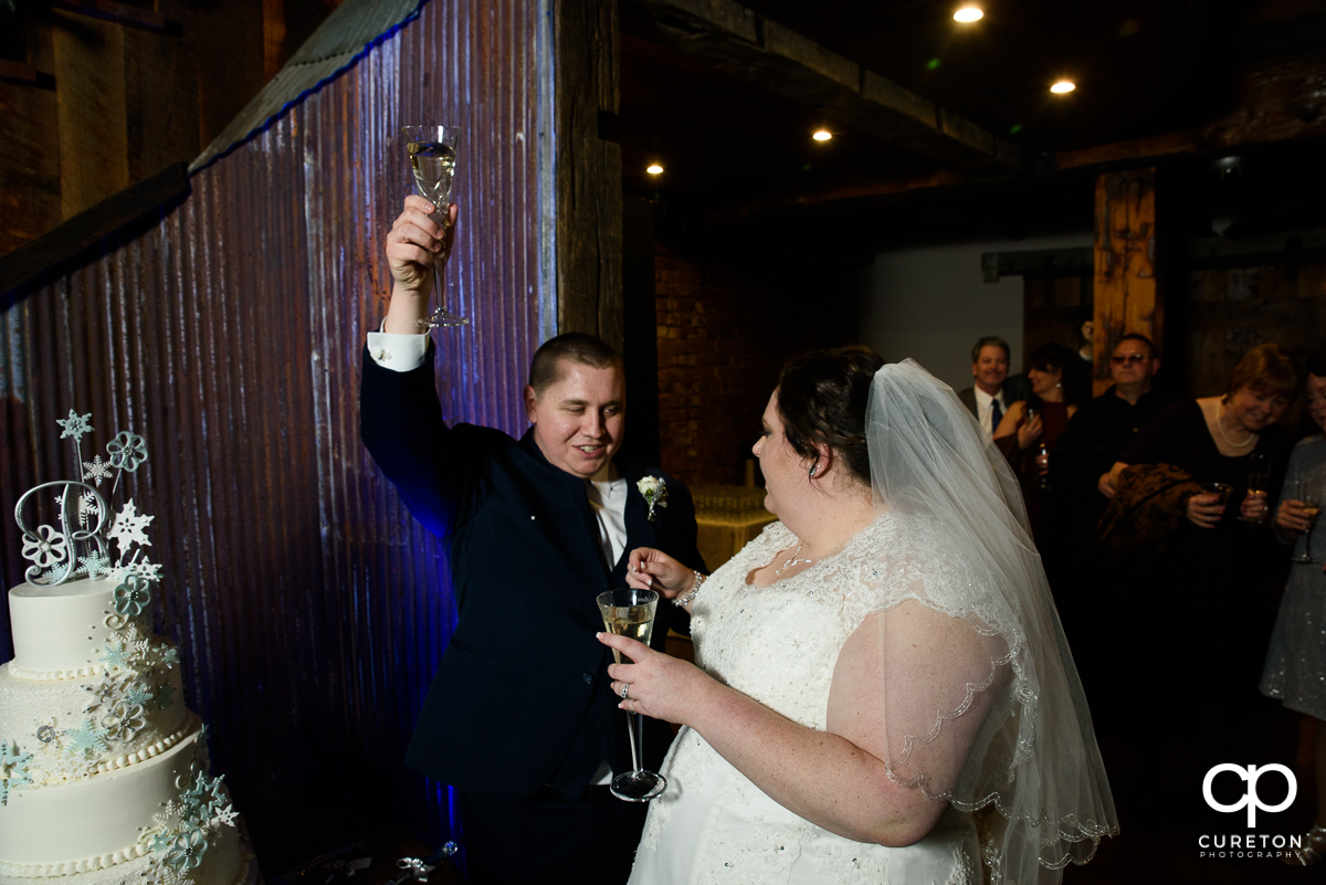 Bride and groom raising a toast.