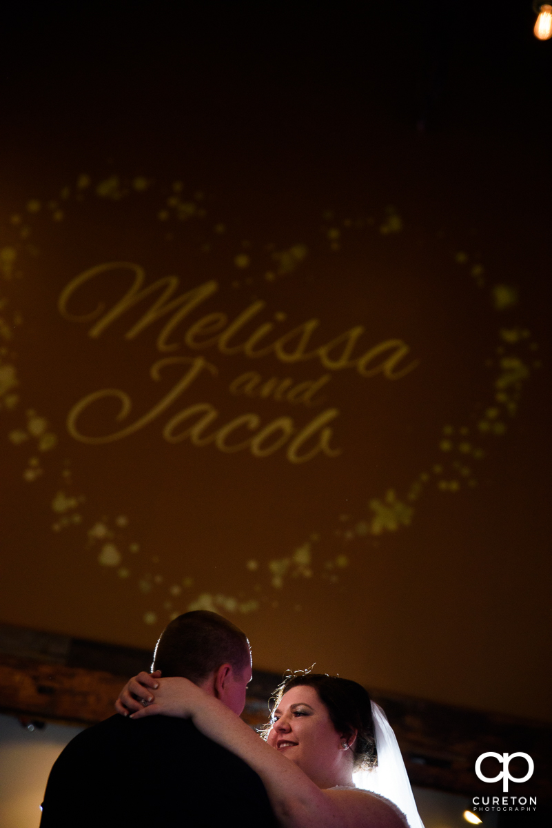 Bride and groom having their first dance with an animated logo in the background.
