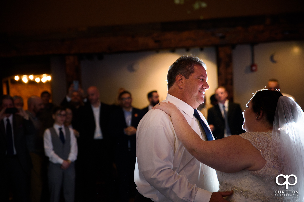 Dad smiling at his daughter as they share a dance at her wedding reception.