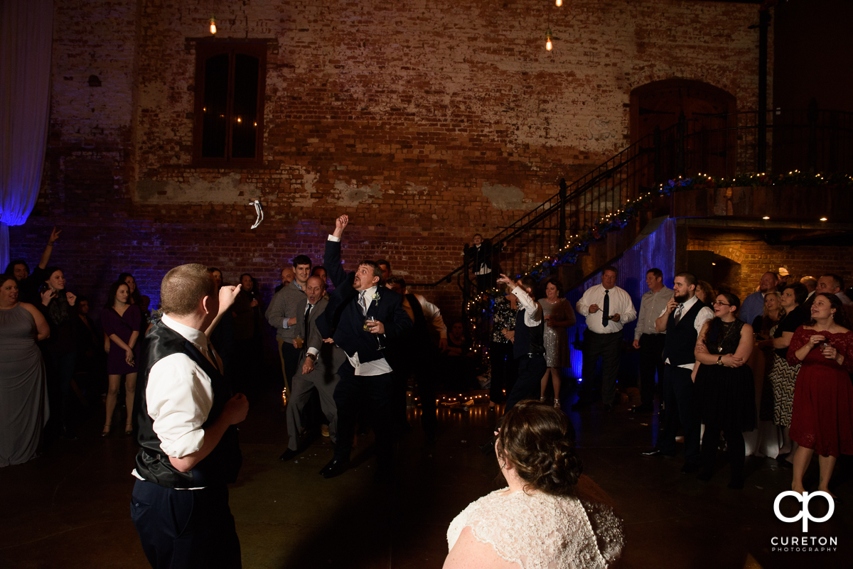 Groomsmen jumping for the garter.