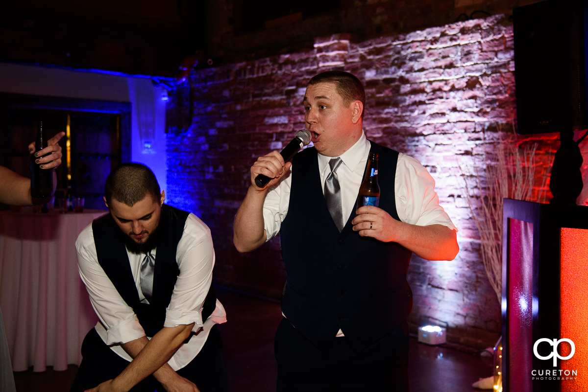 Groom with a microphone at the wedding reception.