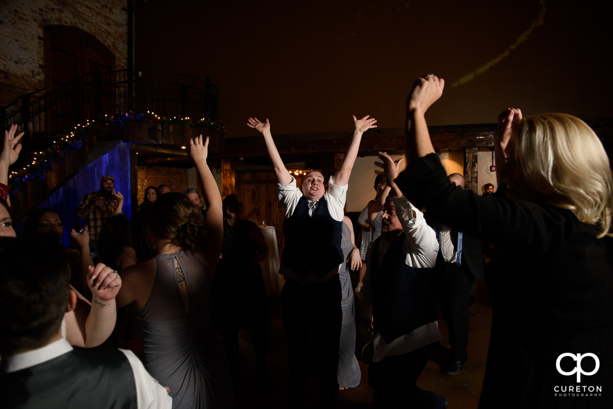 Groom dancing with his hands in the air.