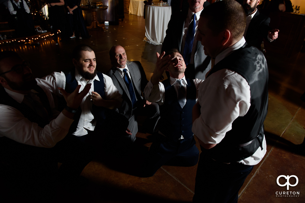 Groomsmen serenading the groom on the dance floor.