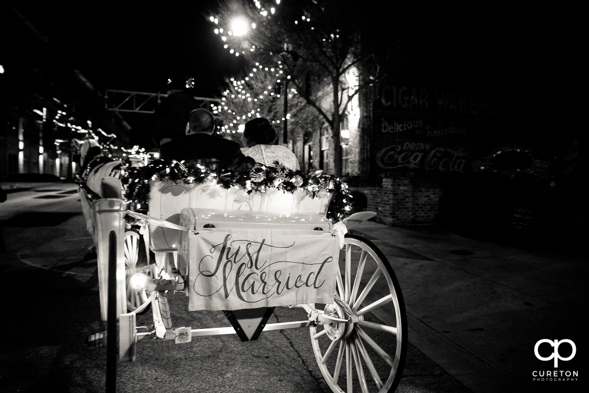 Bride and groom leaving the wedding in a horse drawn carriage in downtown Greenville.