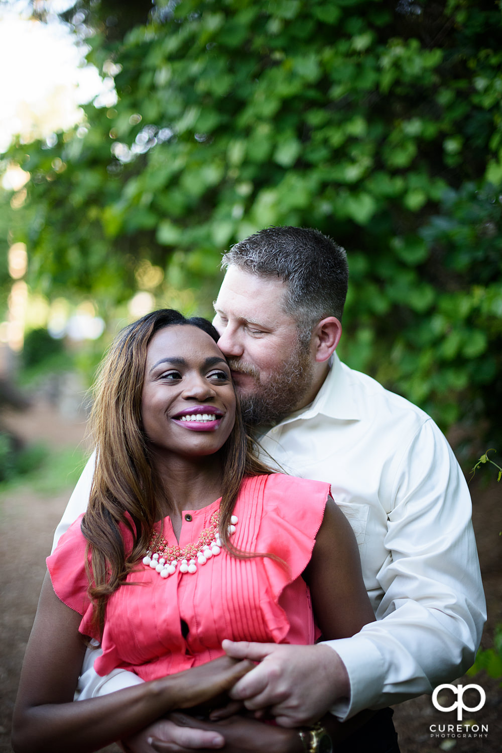 Future groom hugging his bride during their downtown Greenville park engagement session.