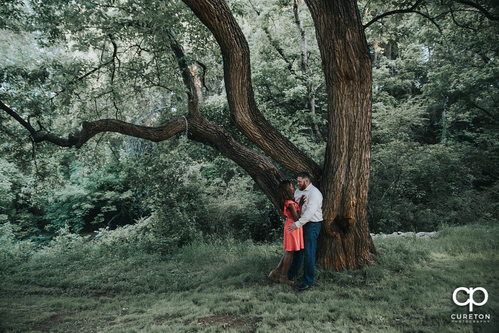 Engaged couple leaning on an oak tree during their downtown Greenville park engagement session.
