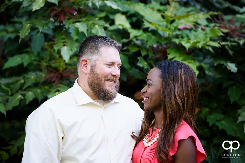Engaged couple smiling.