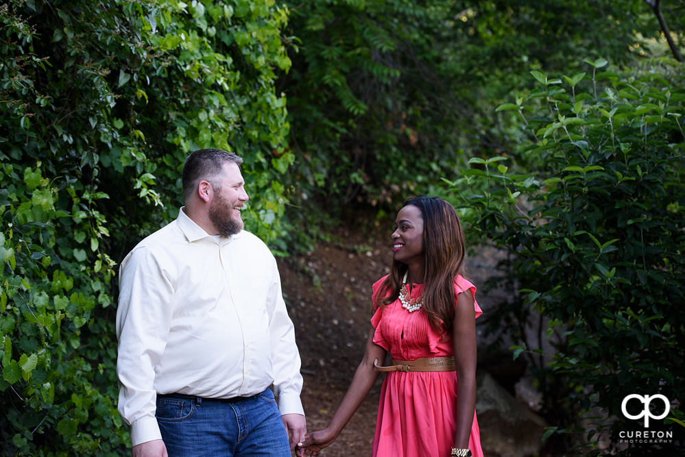 Couple strolling through the trails during their downtown Greenville park engagement session.