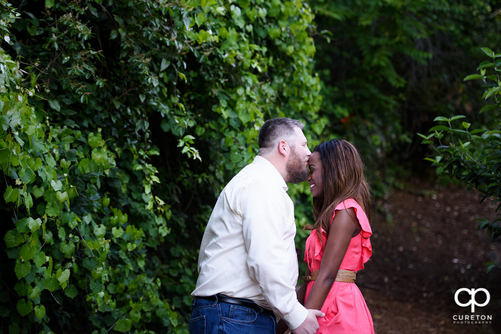 Groom kissing his bride on the forehead during their downtown Greenville park engagement session.