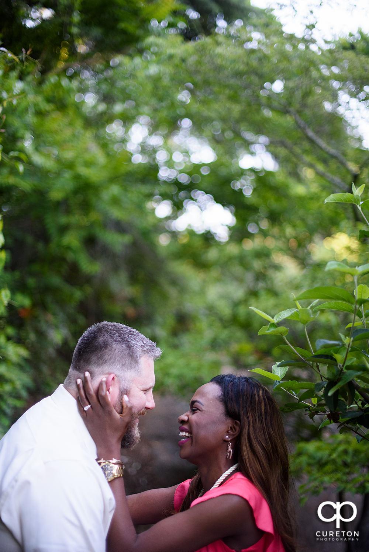 Bride bringing in groom to kiss.