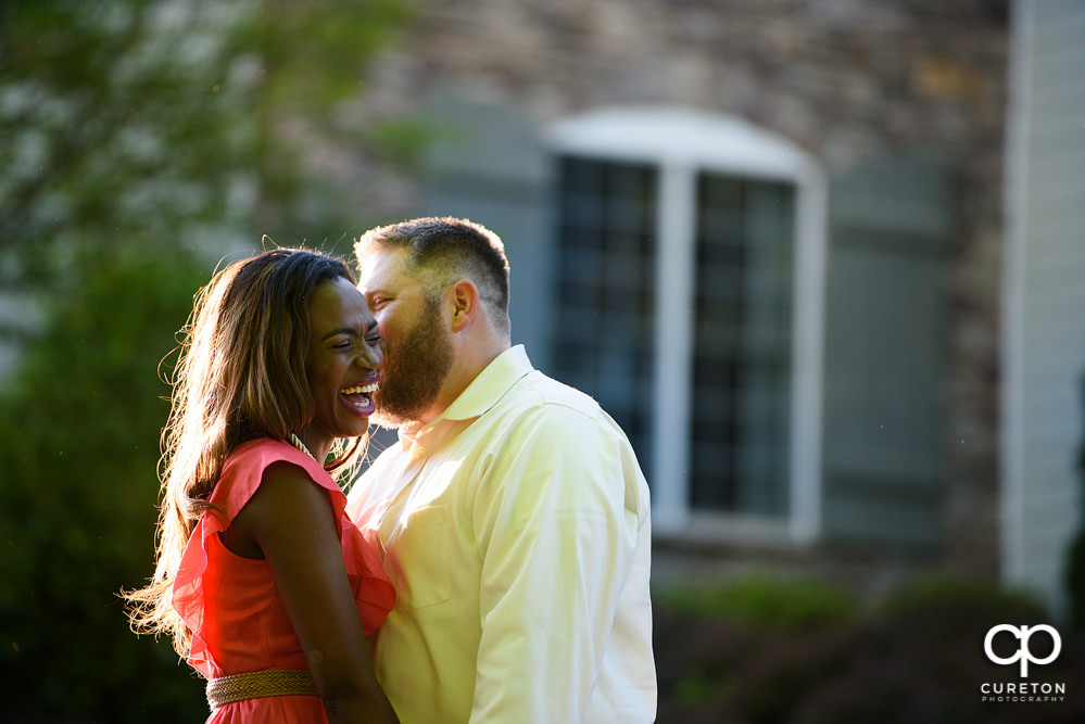 Future groom making his bride laugh during their downtown Greenville park engagement session.