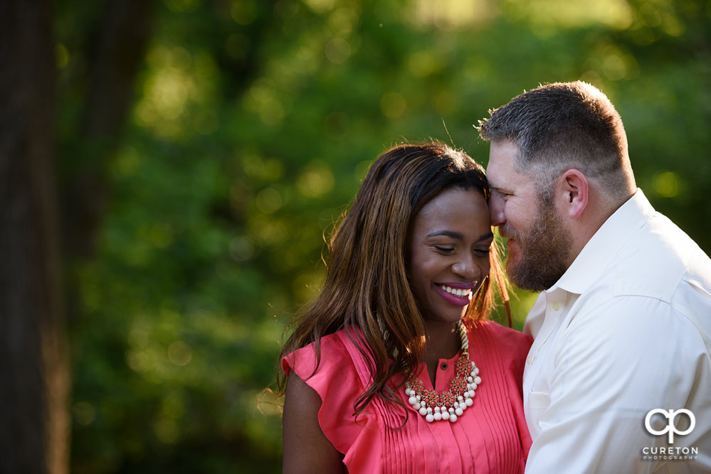 Couple smiling at their engagement session in a park in downtown Greenville.
