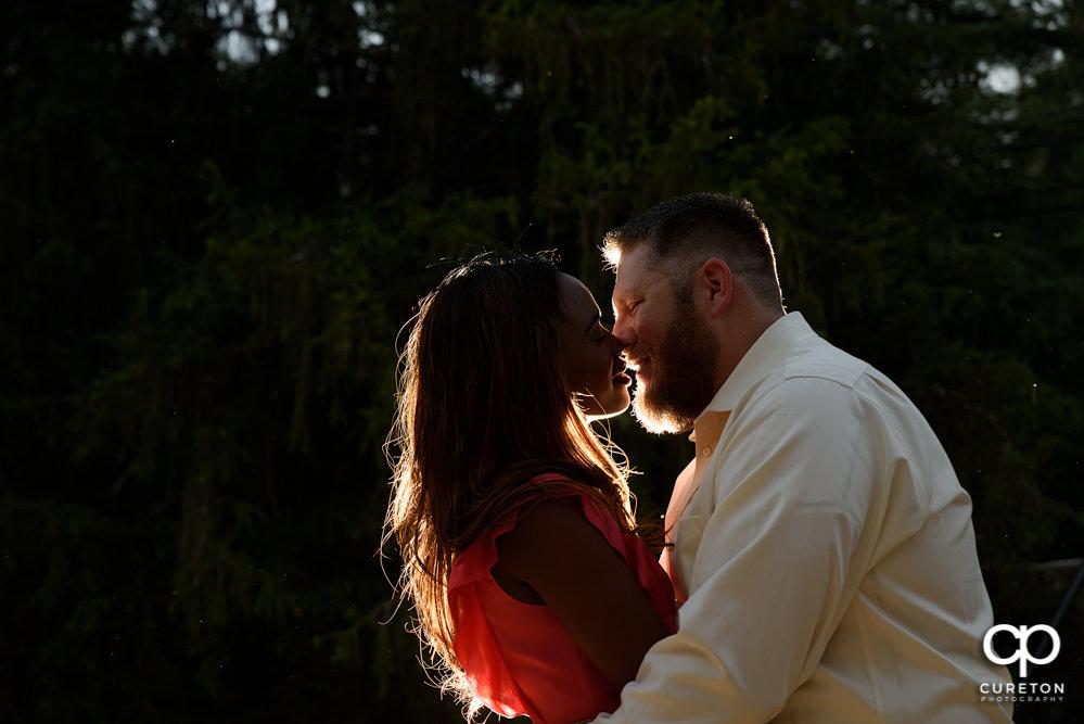Engaged couple kissing at sunset.