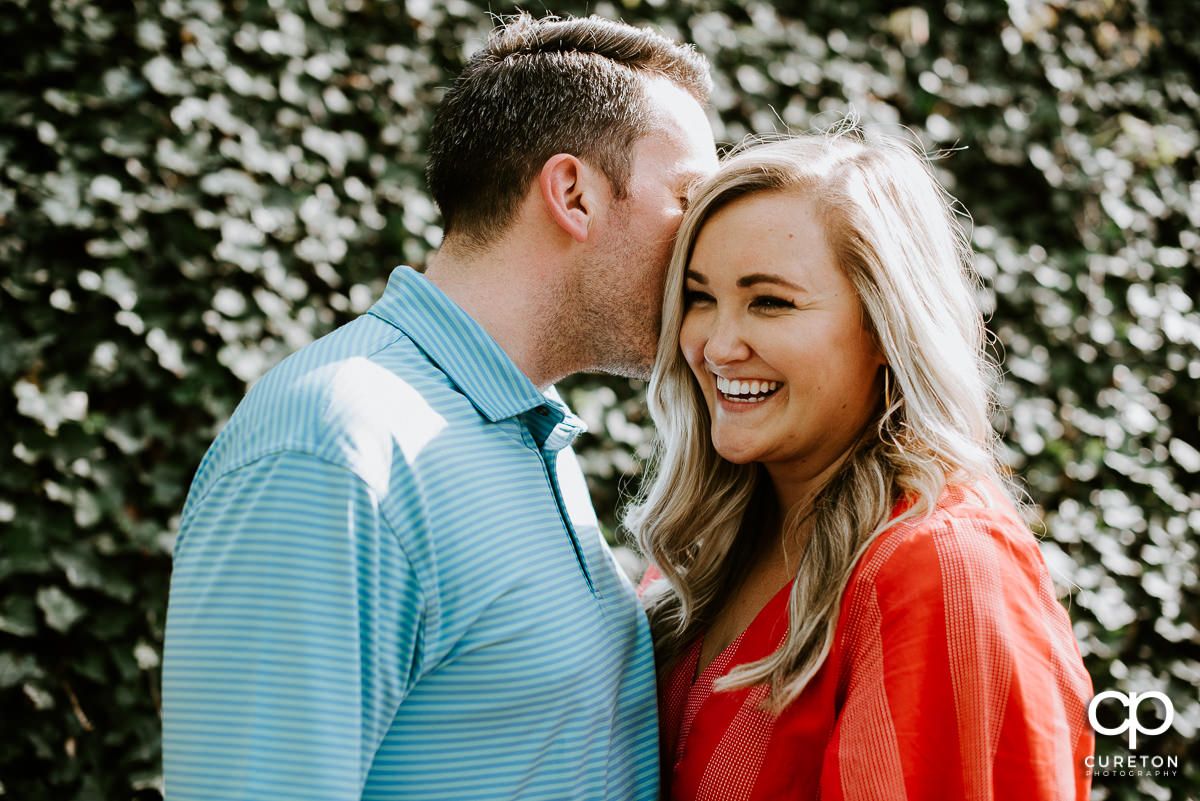 Man whispering into his fiancee's ear.