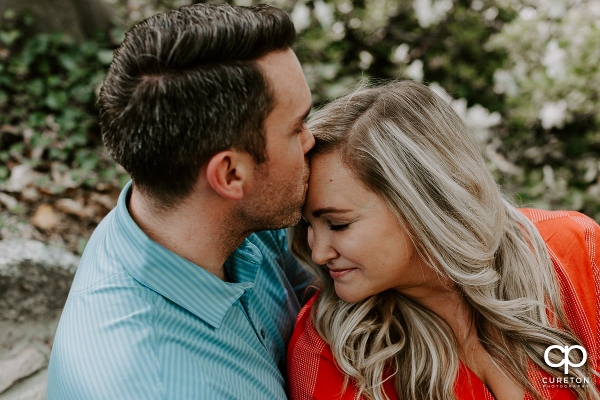 Man kissing his future wife during their engagement session.