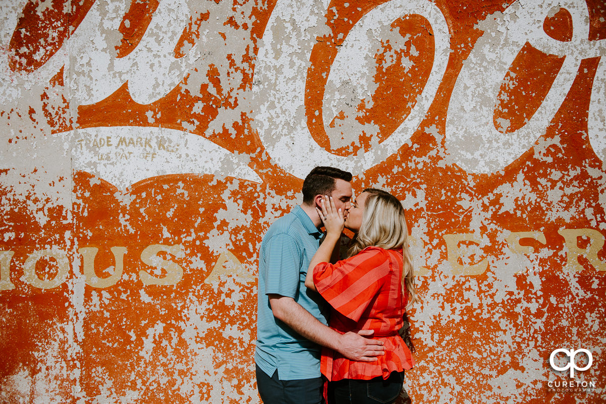 Engaged couple kissing beside a vintage coca cola advertisement on a wall.
