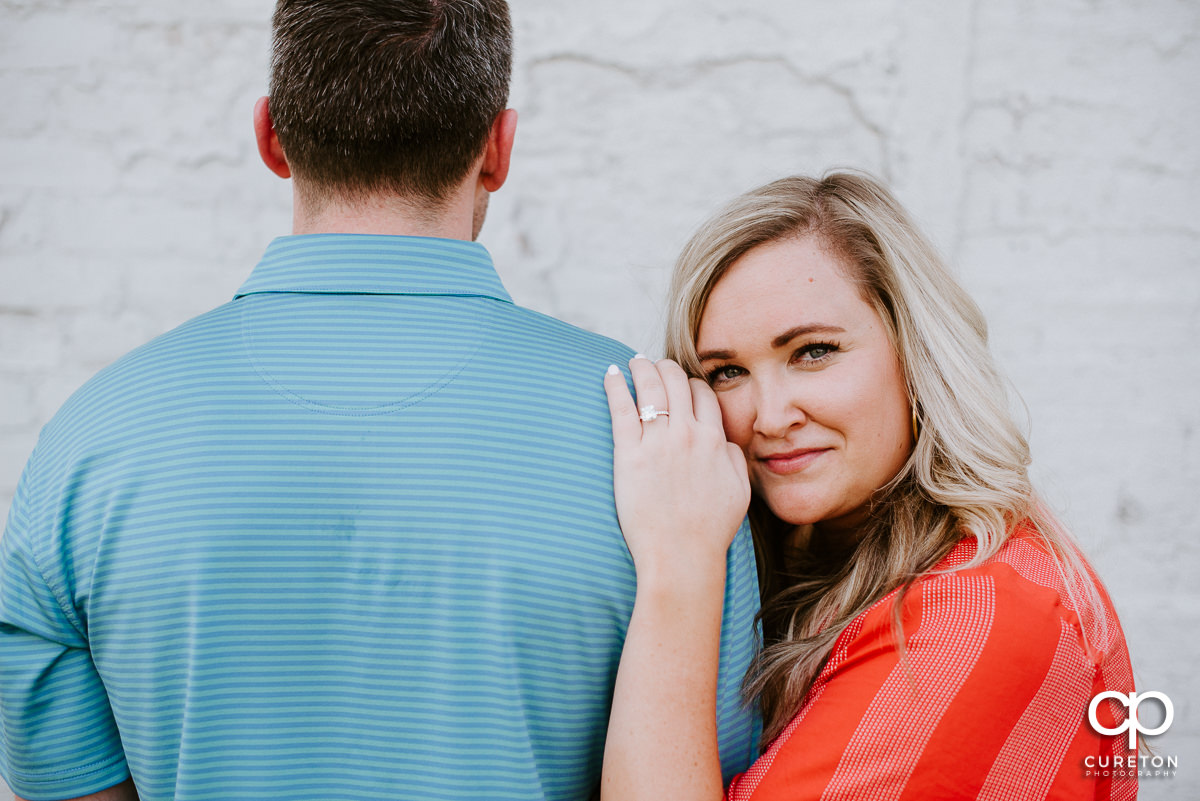 Woman leaning on her fiancee's shoulder and showing off her ring after a surprise proposal in downtown Greenville ,SC.