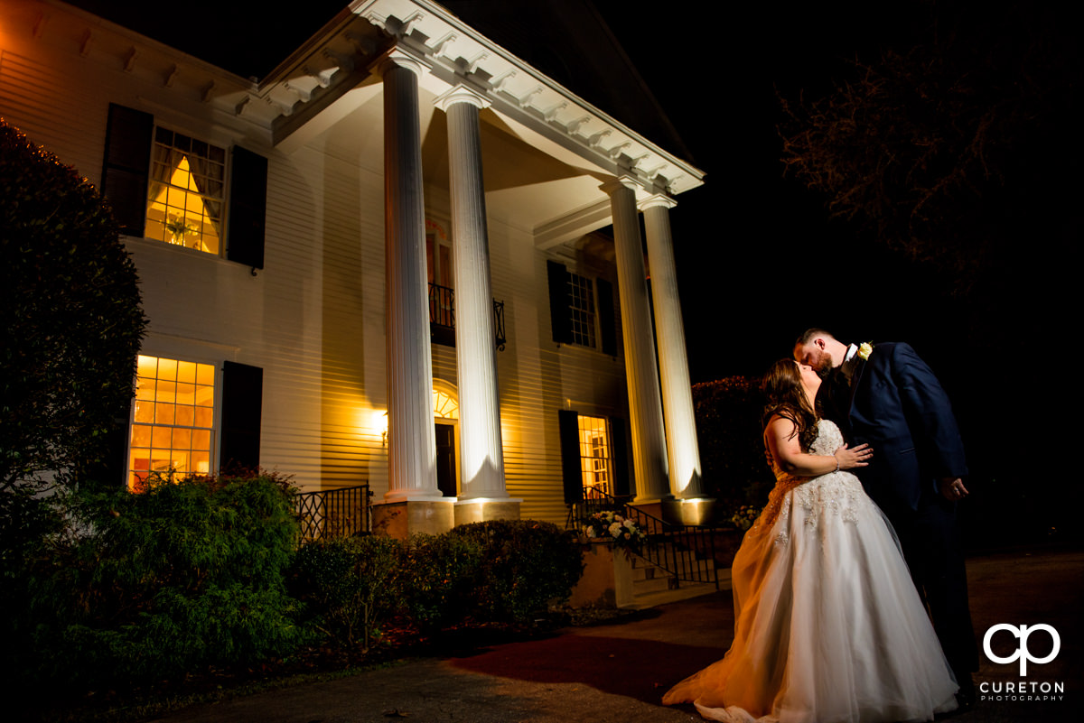 Epic bride and groom night photo in front of the plantation style home during their Duncan Estate wedding in Spartanburg,SC.