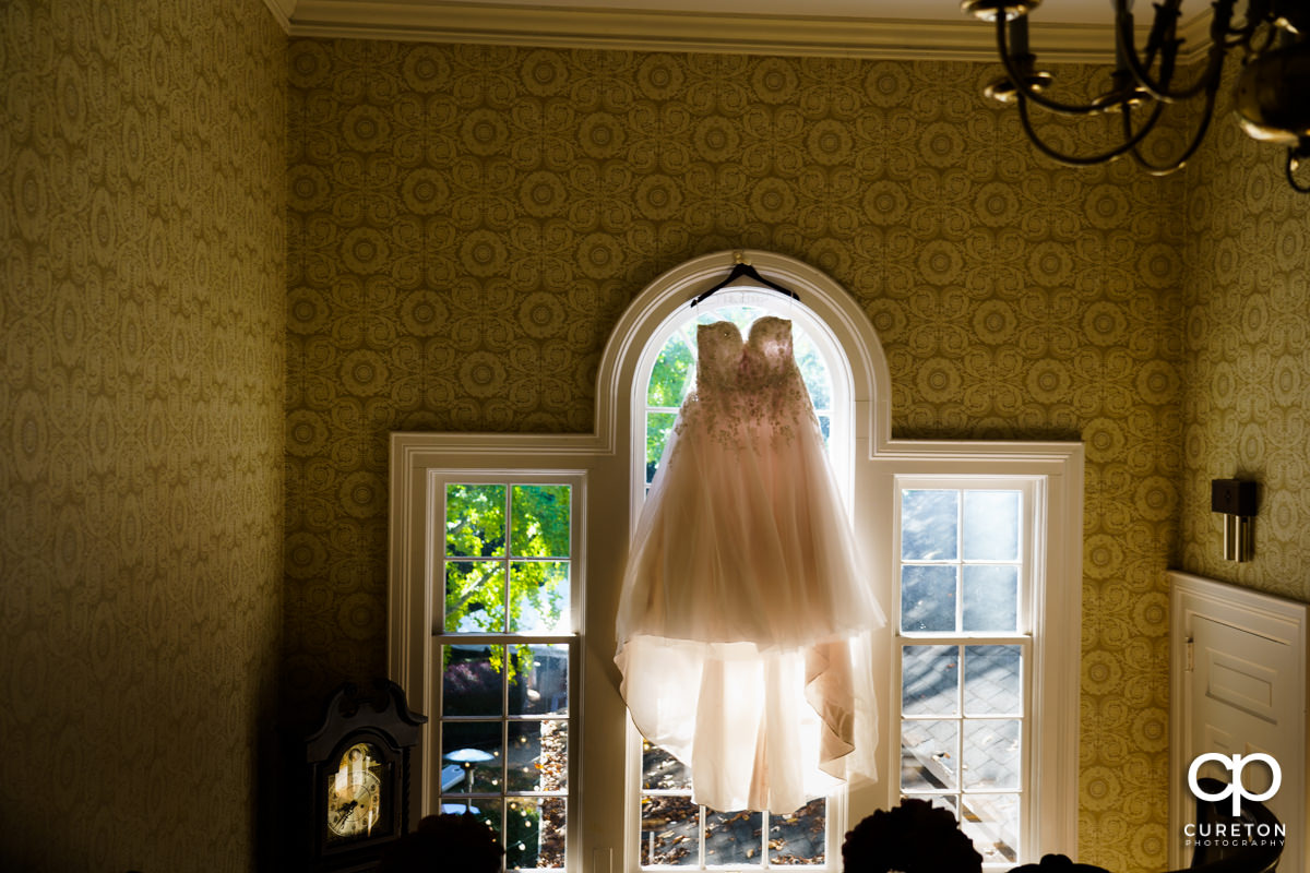 Bride's dress hanging in a window at the Duncan Estate in Spartanburg,SC.