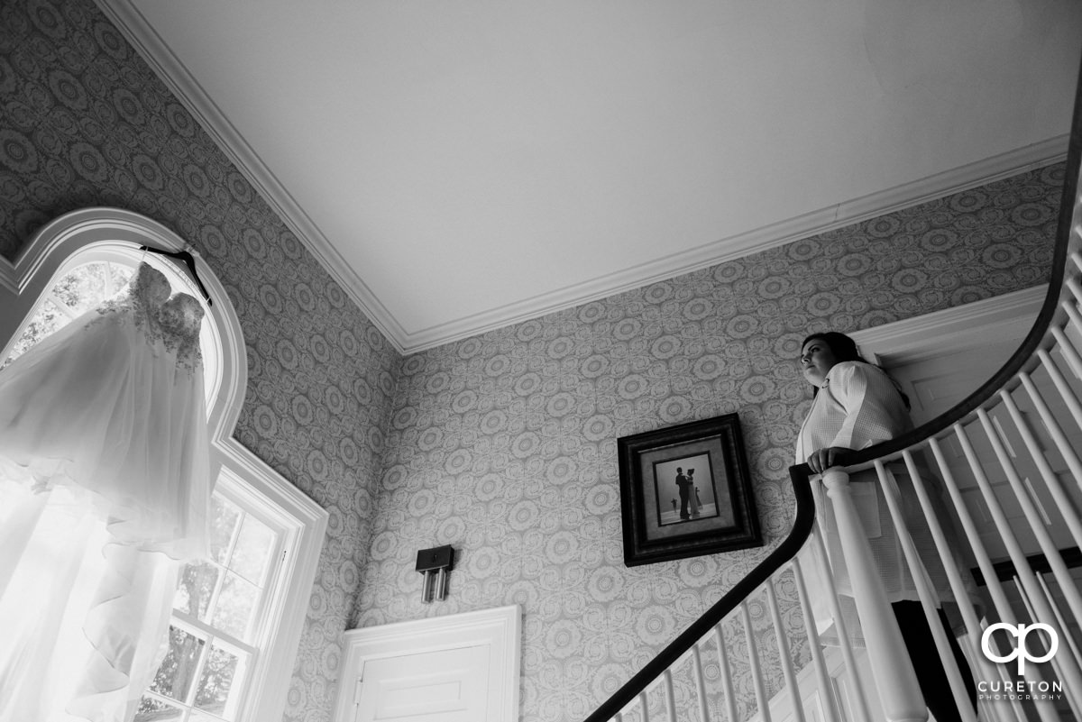 Bride standing on the stairs at Duncan Estate looking at her dress hanging in the window.