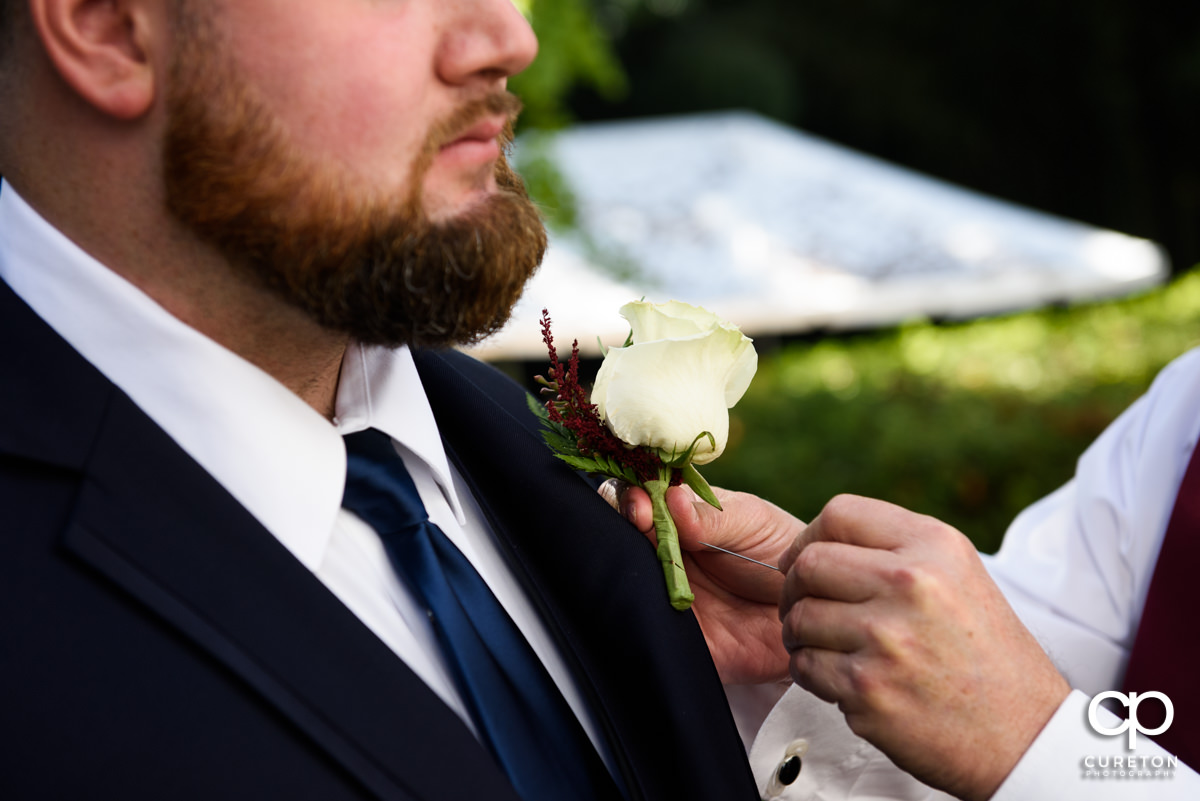 Groom's father helping him pin his boutonniere.