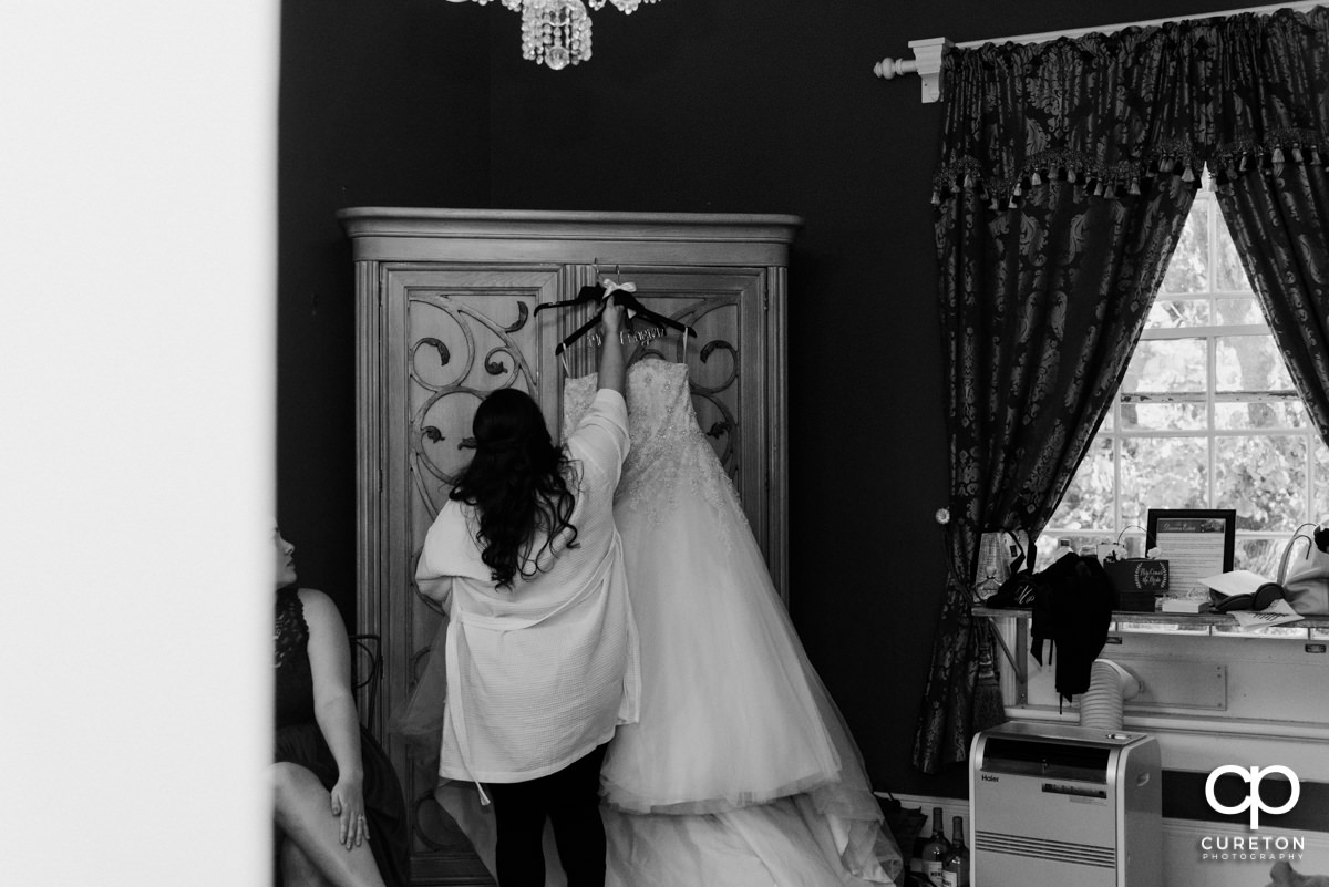 Bride hanging her dress.