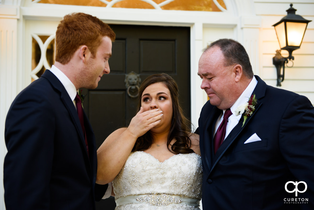 Bride crying while having a first look with her dad and brother before her wedding ceremony.