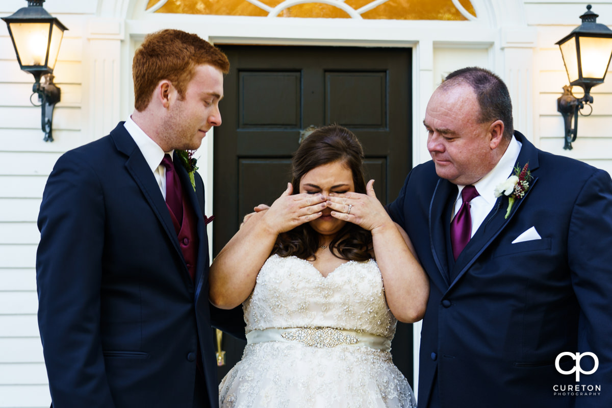Bride wiping away tears while having a first look with her dad and brother before her wedding ceremony.